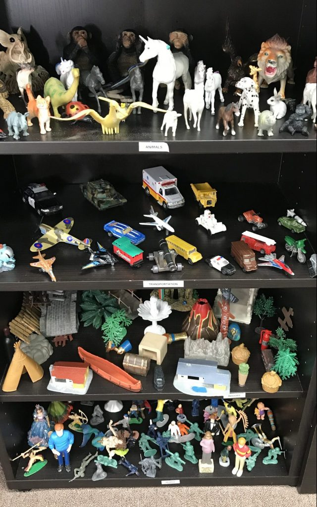 Toy cabinet with a bunch of figurines and other toys for the sand tray used in play therapy near Tampa, FL. You can meet with a play therapist at Sheltering Oaks Counseling for play therapy in Wesley Chapel, FL via online therapy in Florida too!