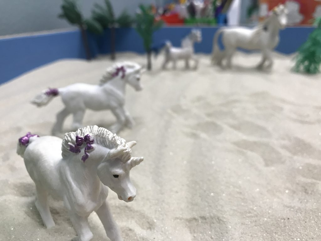 Sand tray with horse figurines for play therapy near Tampa, FL. You can meet with a play therapist at Sheltering Oaks Counseling for play therapy in Wesley Chapel, FL via online therapy in Florida too!