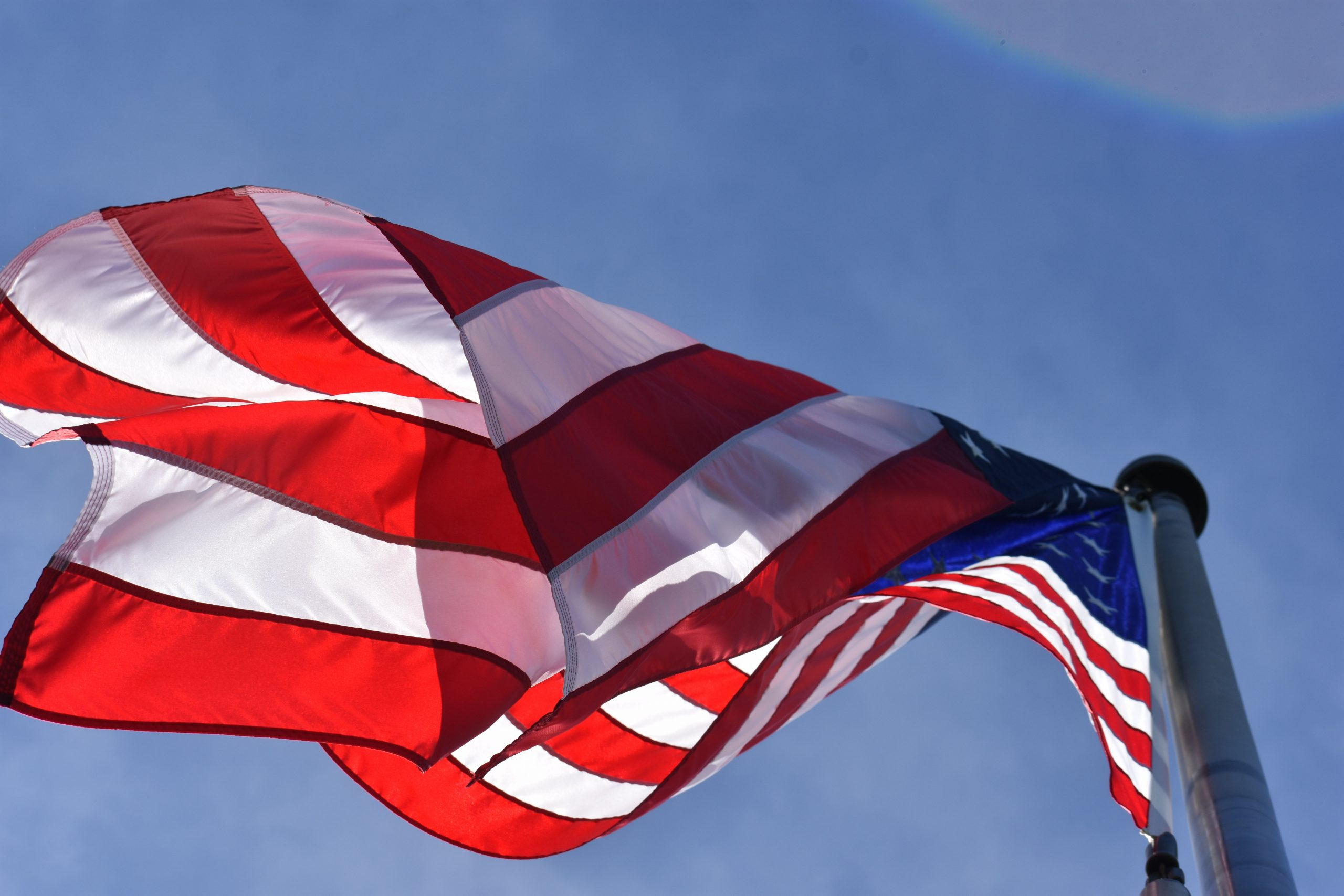 American Flag waving in wind. Veteran mental health disability evaluation for Wesley Chapel, FL and Tampa, FL is available here.
