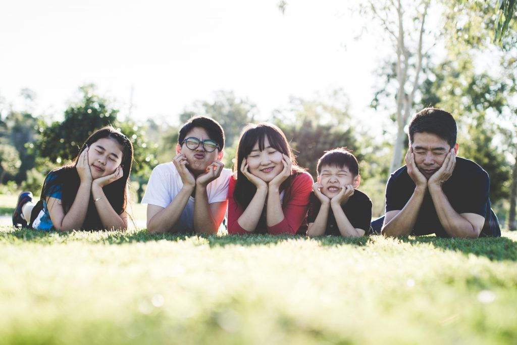 Family portrait of Asian couple with three kids on the grass looking happy after family therapy in wesley chapel, fl. Online therapy in Florida can help with family counseling and couples therapy near Tampa, FL.