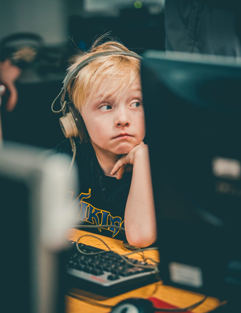 A young child listens to something on the computer as they look off. This could represent ADHD testing in Wesley Chapel, FL. If you are experiencing ADHD symptoms in kids, contact us today for an ADHD assessment.