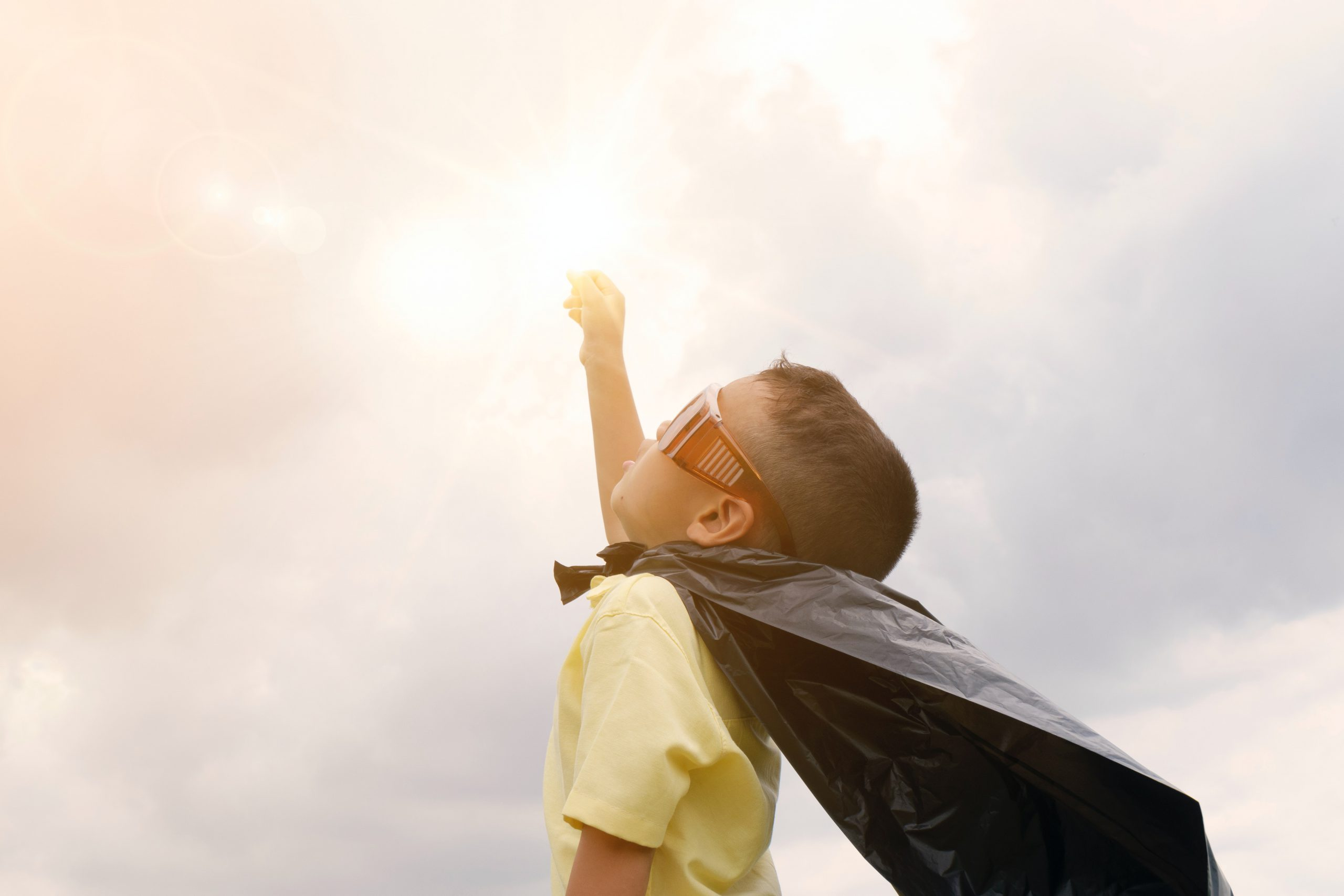 Boy wearing a superman cape looking confident after family therapy in Wesley chapel, fl. Online therapy in Florida can help with family counseling, play therapy  and couples therapy near Tampa, FL.
