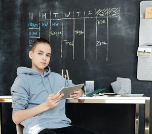 A young teen gives a slight smile as they hold a tablet in their hands. They are sitting in front of a blackboard with a weekly schedule written in chalk. This could symbolize a teen striving for advanced academic achievement. We offer private gifted testing in Wesley Chapel, Fl. Contact us today to learn how private testing for giftedness can support your child.