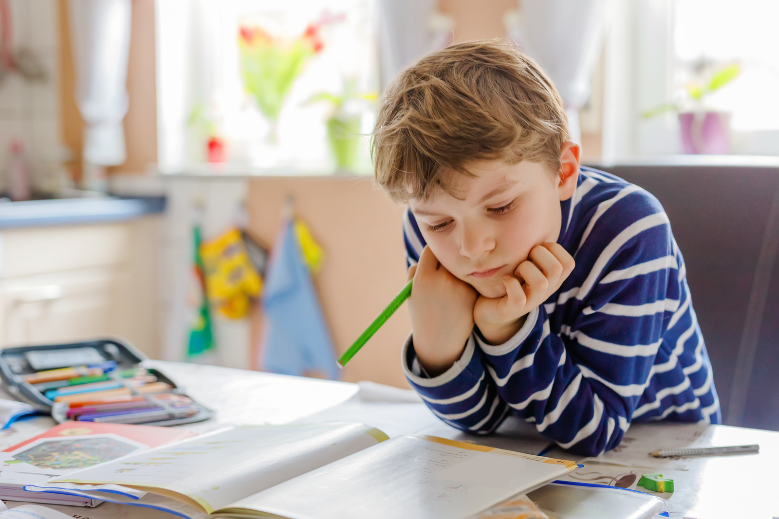 A young student looks at their homework with a confused look. This could represent the difficulties children with ADHD experience. Contact us to learn about ADHD testing near Tampa, FL, and if an ADHD test for kids can offer you support!
