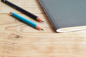 Two sharpened pencils rest next to a closed notebook on a desk. This could symbolize untapped creativity from an individual who doesn't yet know they are gifted. We offer gifted testing in Wesley Chapel, FL. Contact us to learn more about private testing for giftedness. A gifted IQ test can help you better understand your child's unique needs.