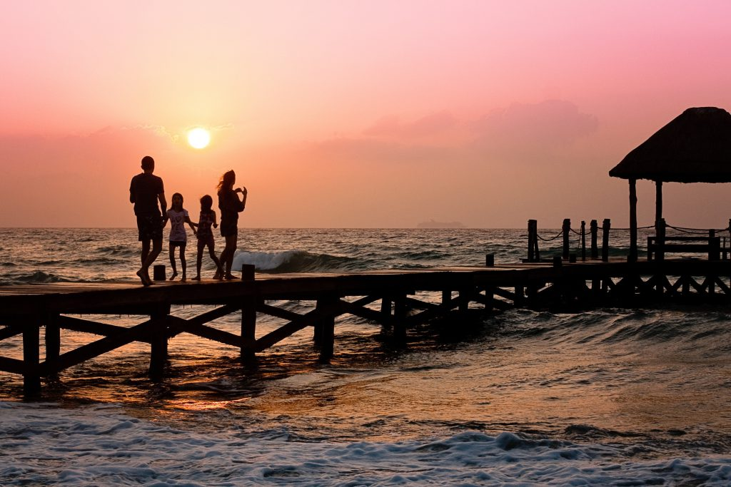 Family at a beach near the ocean at sunset. This family became happier with family christian counseling in wesley chapel, fl. If you're are looking for christian therapy tampa fl. In fact if you are a pastor, Sheltering Oaks Counseling counseling for ministers.