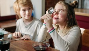 A girl makes a funny face into a magnifying glass as their lab partner watches entertained. This could represent the difficulties with attention that come with ADHD. We offer ADHD testing in Florida, ADHD testing near Tampa, FL, and other services! Contact us and learn more about our ADHD test for children.