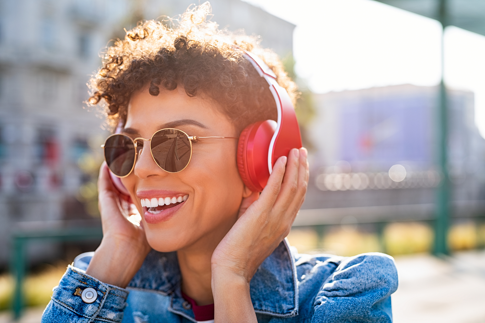 Young smiling african woman listening music with headphones at sunset after trauma therapy tampa, FL and PTSD treatment in Wesley Chapel, FL