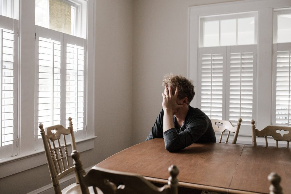 Man with hand on face sitting at the kitchen table looking out the window needs young adult counseling near Tampa, FL. Sheltering oaks provides therapy for young adults in Wesley Chapel, FL. You can get help with online therapy in Florida for millennials here!