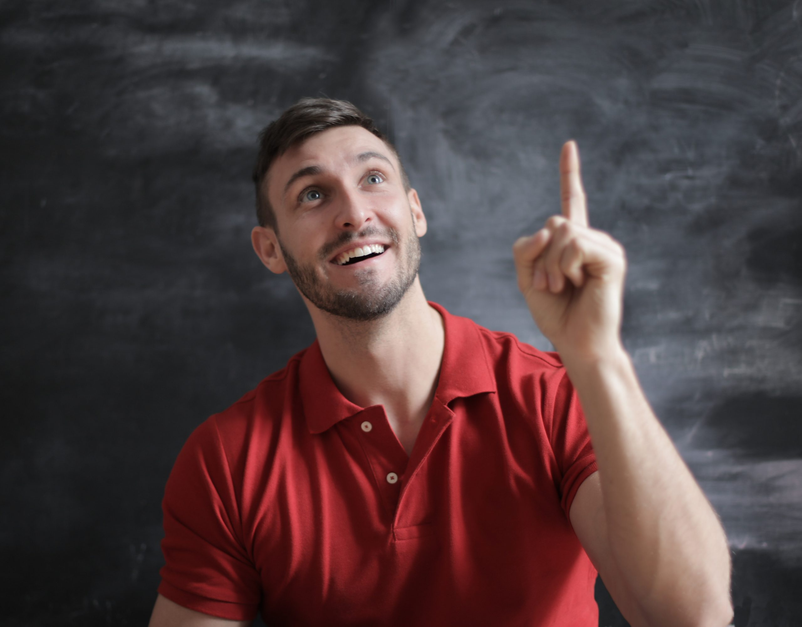 Man in red shirt against grey background smiling and pointing up to God after Christian counseling in Tampa, FL at Wesley Chapel counseling clinic Sheltering Oaks. You can get online therapy in Florida here with a christian counselor!