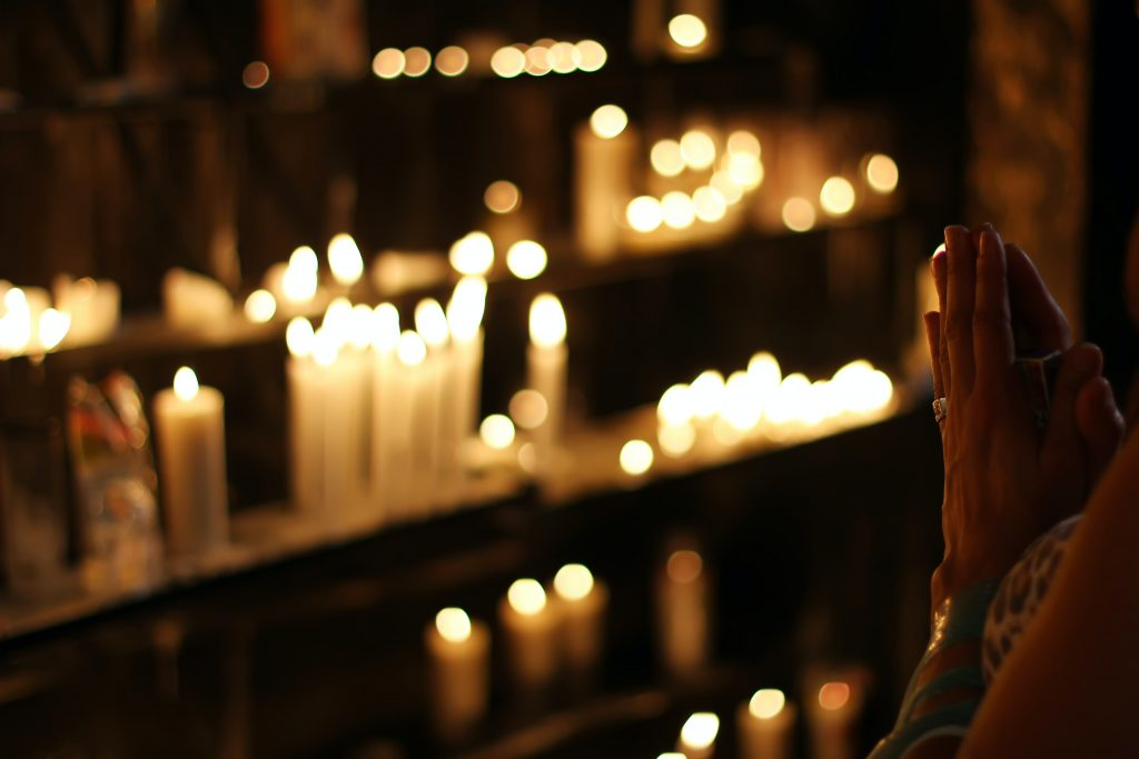 Person praying with prayer candles needs Christian counseling in Tampa, FL at Wesley Chapel counseling clinic Sheltering Oaks. You can get online therapy in Florida here with a christian counselor!