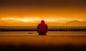 Person sitting by water in the sunset. Get autism testing and evaluation near Tampa, FL