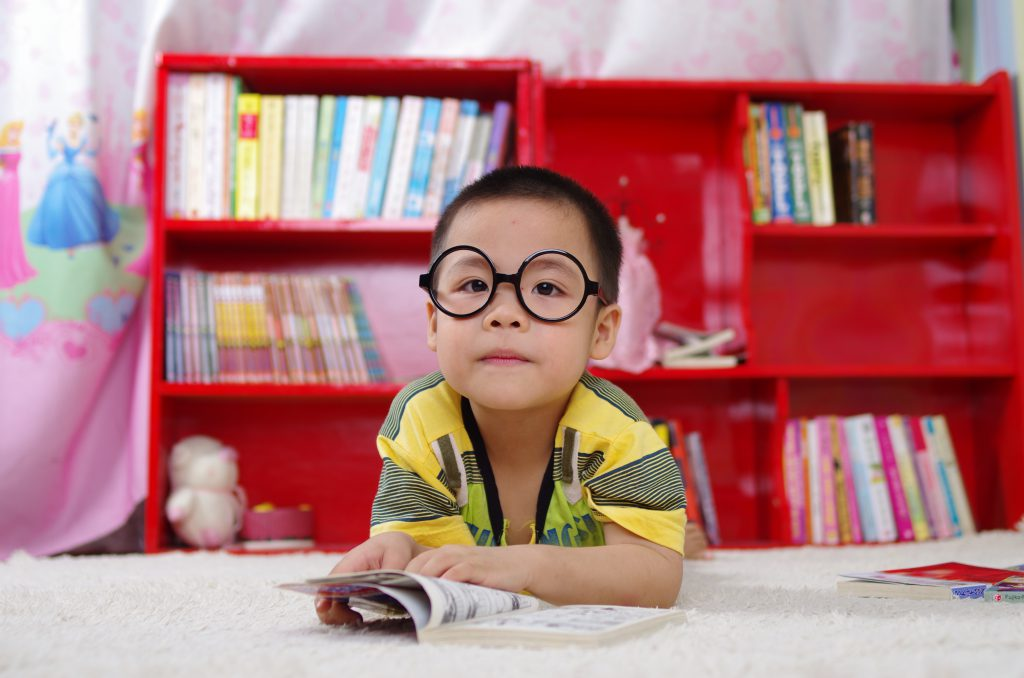 A lone young Asian child wearing glasses rests against a table with an open book flipped to a random page. This could symbolize the preference for solitude, a common sign of autism. Contact us for a child autism test in Wesley Chapel, FL to better understand your child's behaviors and needs.