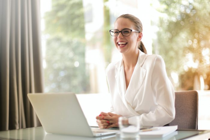 Woman at a desk smiling and happy with her work around in a brightly lit room with a window behind her. Can get help with neuropsychological testing in Tampa, FL at Sheltering Oaks Counseling in Wesley chapel, FL or in online therapy in Florida