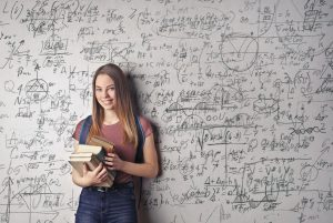 A teen girl smiles with books in hand as she stands in front of a whiteboard covered in equations. This could represent the potential of a gifted student. We offer private testing for giftedness in Wesley Chapel, FL. Contact us to learn more about private gifted testing today.