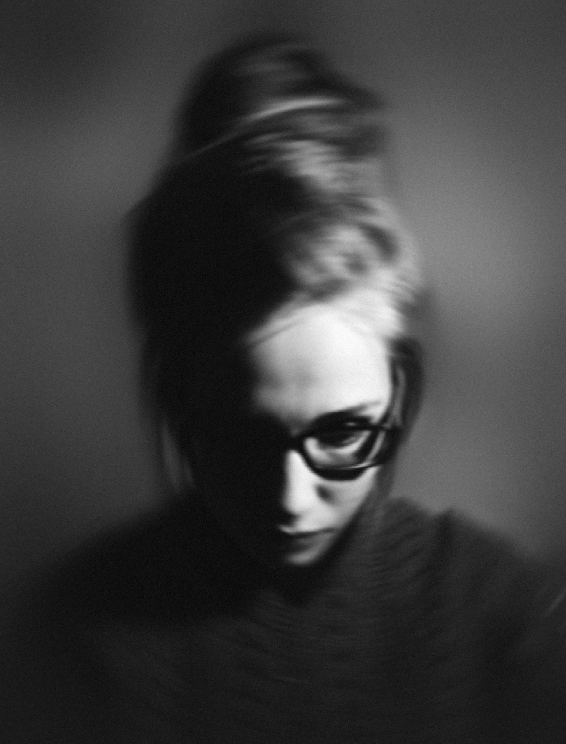 Woman with glasses looking down and sad in blurry black and white photo. She needs Trauma Therapy near Tampa, FL at Sheltering Oak Counseling for PTSD Treatment in Wesley Chapel, FL