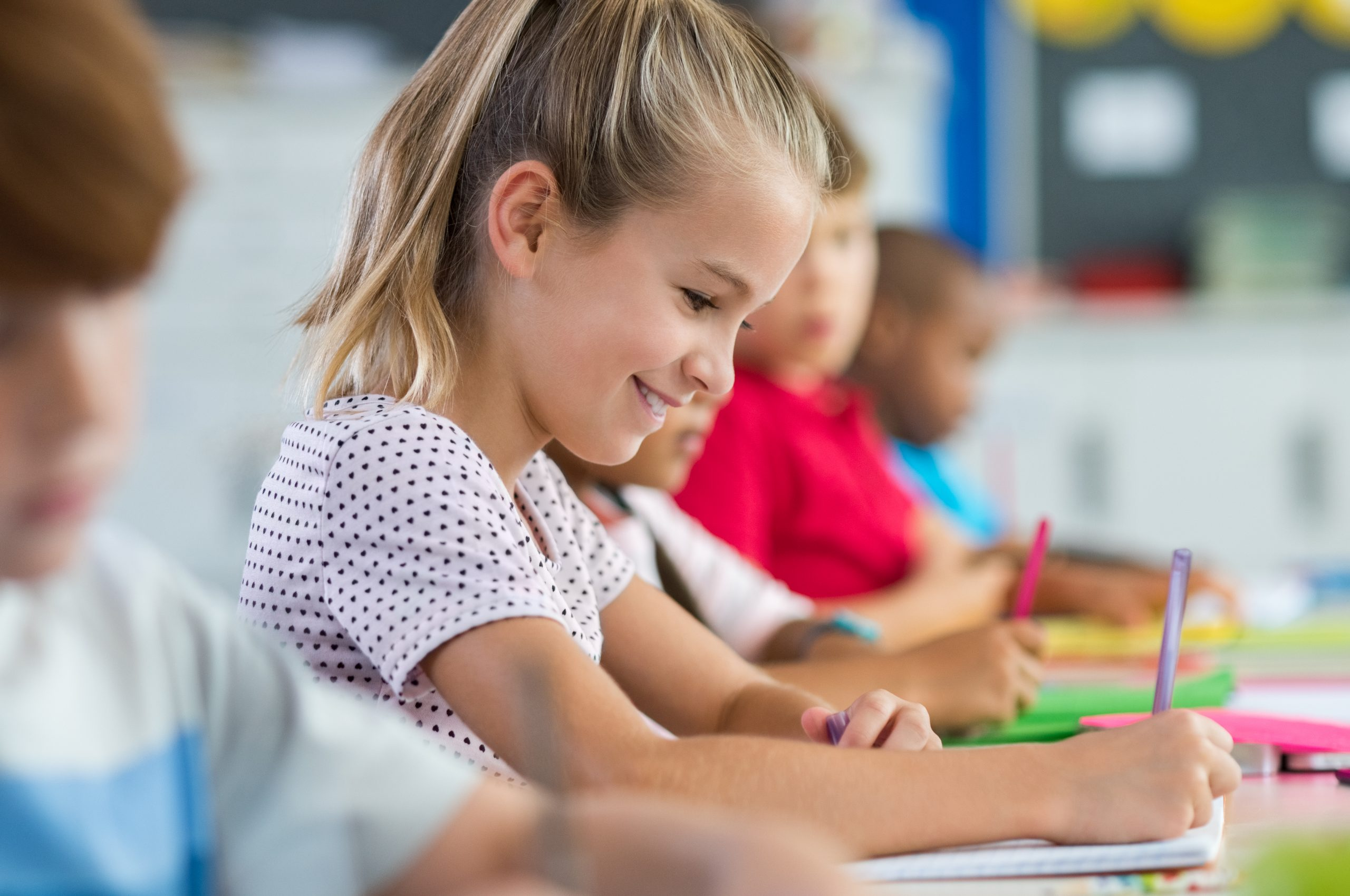 """A young schoolgirl smiles as she writes on the paper in front of her. This could represent the benefits of psychoeducational testing in Tampa, FL. Search """"psychoeducational testing near me"""" to learn more about psych-ed testing today."""